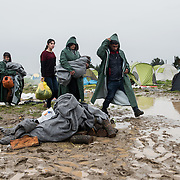 A family of refugees walk with all the possessions wrapped in UNHCR blankets in a flooded muddy field near the transit camp of Idomeni, Greece. <br /> <br /> Thousands of refugees are stranded in Idomeni unable to cross the border. The facilities are stretched to the limit and the conditions are appalling.