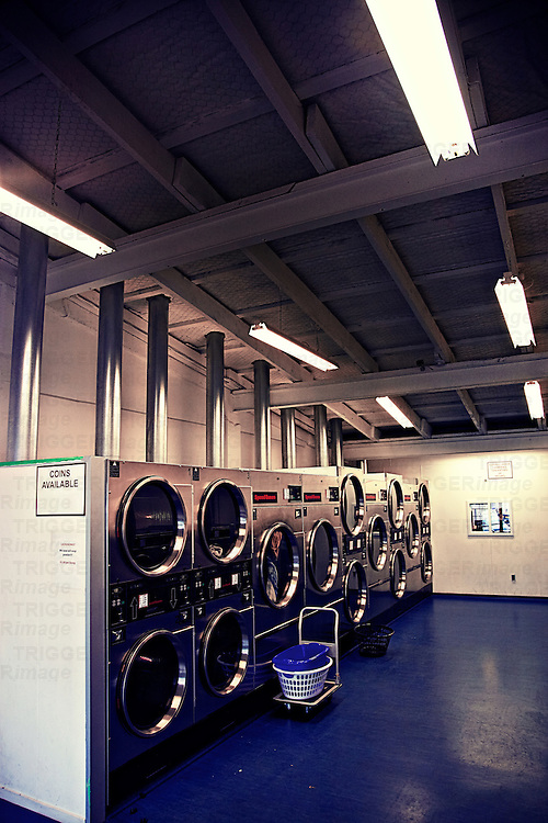 row of washing machines in an empty launderette