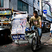MANILA (Philippines). 2009. Tricycle in Manila. The tricycle is a little, roofed sidecard bolted to a bycicle and is one of the most popular  transports for short journeys in Manila.