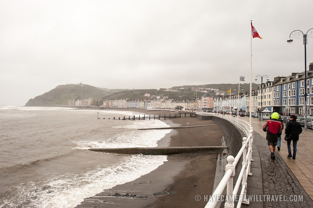 A few pedestrians brave the windy and wet weather to walk along the waterfront in Aberystwyth on the western coast of Wales.