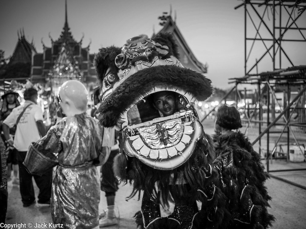 """14 MARCH 2014 - NAKHON CHAI SI, NAKHON PATHOM, THAILAND: A member of a lion dance troupe waits to perform during the tattoo festival at Wat Bang Phra. Wat Bang Phra is the best known """"Sak Yant"""" tattoo temple in Thailand. It's located in Nakhon Pathom province, about 40 miles from Bangkok. The tattoos are given with hollow stainless steel needles and are thought to possess magical powers of protection. The tattoos, which are given by Buddhist monks, are popular with soldiers, policeman and gangsters, people who generally live in harm's way. The tattoo must be activated to remain powerful and the annual Wai Khru Ceremony (tattoo festival) at the temple draws thousands of devotees who come to the temple to activate or renew the tattoos. People go into trance like states and then assume the personality of their tattoo, so people with tiger tattoos assume the personality of a tiger, people with monkey tattoos take on the personality of a monkey and so on. In recent years the tattoo festival has become popular with tourists who make the trip to Nakorn Pathom province to see a side of """"exotic"""" Thailand.   PHOTO BY JACK KURTZ"""