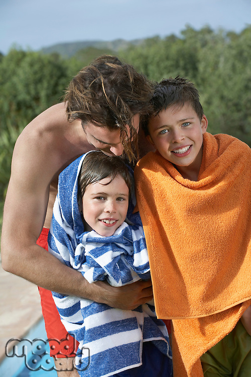 Father and two boys (6-11) wrapped in towels