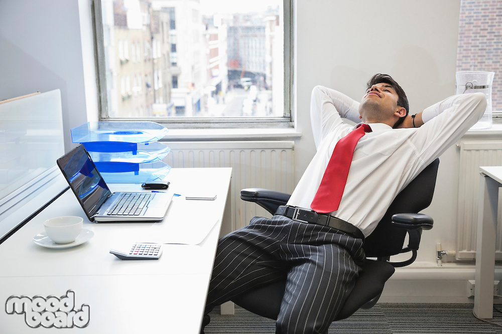 Young Indian businessman relaxing in chair at office desk