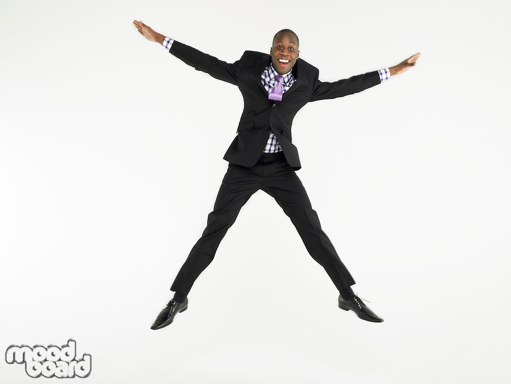 Man in suit jumping in star shape in studio