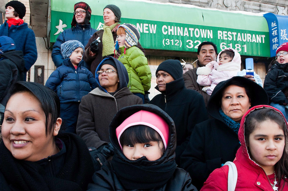A crowd looks on in front of the New Chinatown Restaurant during the Chinese New Year parade in Chicago, 2010