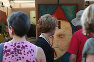Visitors admire whimsical mixed media painting with figurine at the St. Louis Art Fair; Clayton, Missouri.
