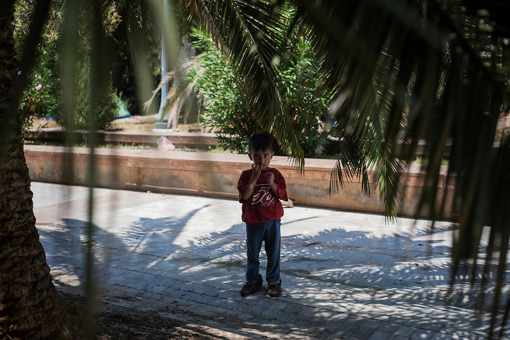 Greece, Athens, July 25th 2015 - An Afghan boy at Pedion tou Areos park where hundreds of migrants and refugees mostly from Afghanistan have build a temporary camp, after they arrived in Athens from the Greek islands, wishing to continue their journey to central Europe.
