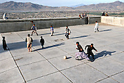 Boys playing soccer at an abandoned Soviet-era swimming pool on a hilltop overlooking Kabul, Afghanistan. 2002