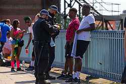 Police search two young men as they arrive at the carnival on Ladbroke Grove as day one, Children's Day, of the Notting Hill Carnival gets underway in London. London, August 25 2019.
