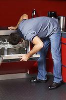 Young man looking at dish washer