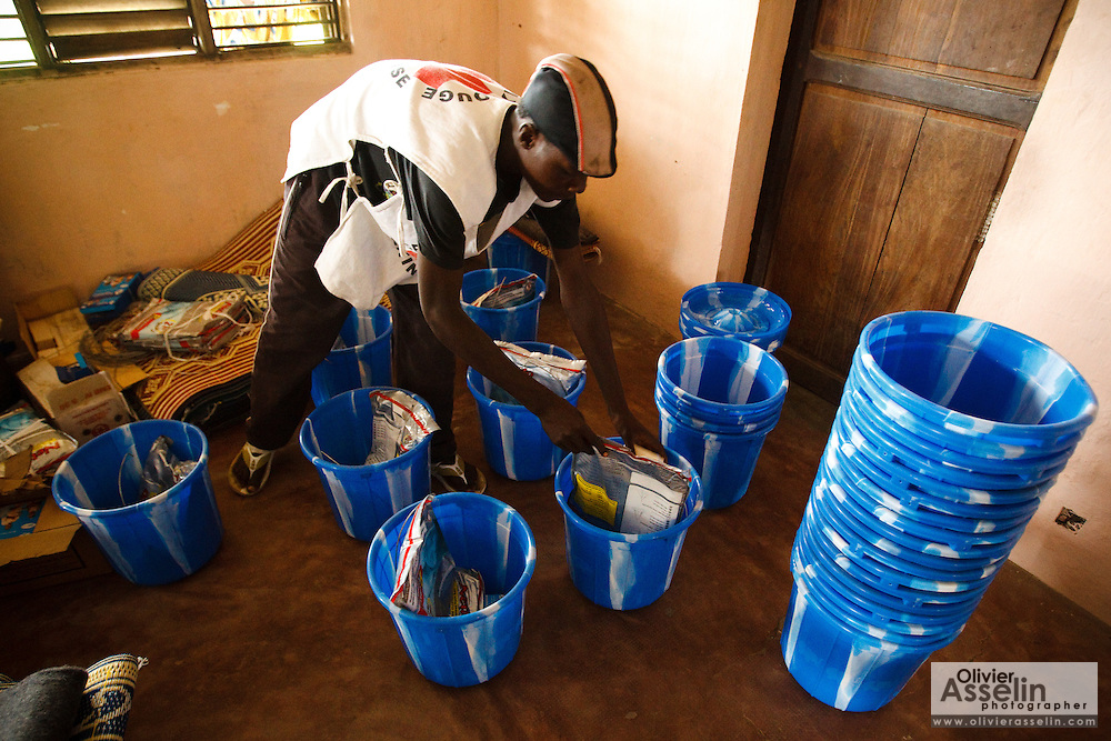 A Benin Red Cross volunteer assembles kits for flood victims during a UNICEF-sponsored distribution session in Athieme, Benin  on Monday October 25, 2010. UNICEF donated water treatment tablets, mosquito nets and soap to affected families, while other partner organizations offered blankets, floormats, and buckets.