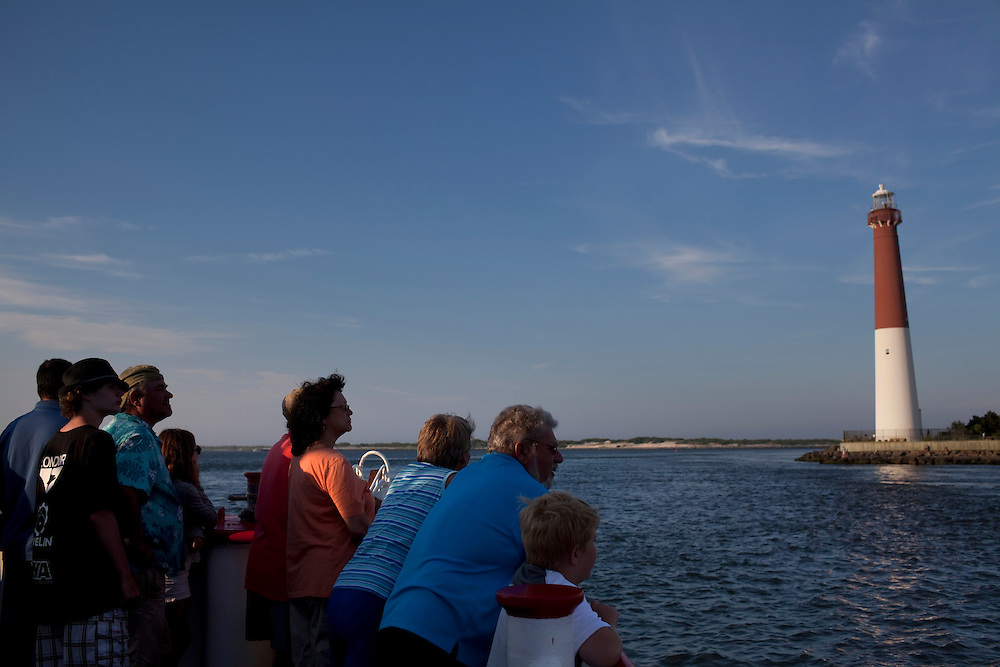 Long Beach Island, NJ - June 29, 2013 :  Visitors on Miss Barnegat Light sunset cruise sail past Barnegat Lighthouse, built in 1857, on the northern tip of Long Beach Island, NJ on June 29, 2013. People are returning to the beaches for the summer after recovery efforts post Superstorm Sandy.