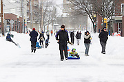 Pedestrians make their way down College Avenue in Davis Square in Somerville, Massachusetts, U.S., after Winter Storm Nemo dropped about 2 feet of snow overnight on Saturday, Feb. 9, 2013. Mass. Gov. Deval Patrick imposed a road travel ban until road conditions improve. Photographer: Kelvin Ma/Bloomberg