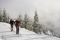 Two cross country skiers cruise along the Puyallup Ridge Trail of the Mount Tahoma Trails hut to hut cross country ski trail system near Mount Rainier in the Cascade Range of Washington, USA.