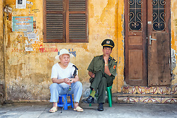 Policeman and man sit on the sidewalk of a street, Hanoi, Vietnam, Southeast Asia