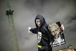 """© Licensed to London News Pictures . 05/11/2019. London, UK. A man holds """" Free Assange """" poster in front of Nelson's Column in Trafalgar Square . Supporters of Anonymous , many wearing Guy Fawkes masks , attend the Million Mask March bonfire night demonstration , in Trafalgar Square in central London . Photo credit: Joel Goodman/LNP"""