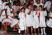 Poutasi Village church, Western Samoa on White Sunday. White Sunday (also called Children's Day) is celebrated on the second Sunday of October each year. In this tradition brought to the island by the London Missionary Society, the children receive new clothes and gifts, and festive games are played. Most attend church services and then gather for family feasts that feature foods like pork, taro, and coconuts. Material World Project.