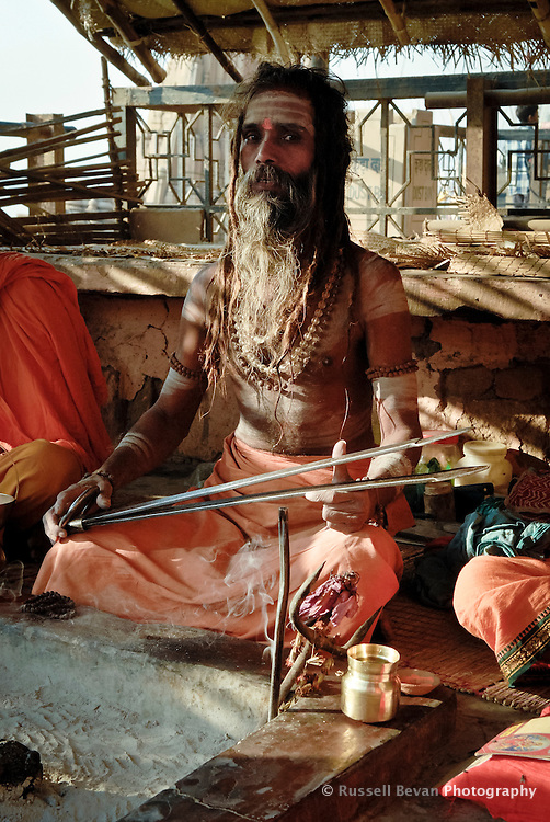 A Hindu holy man playing chimta at the ghats in Varanasi, Uttar Pradesh, India