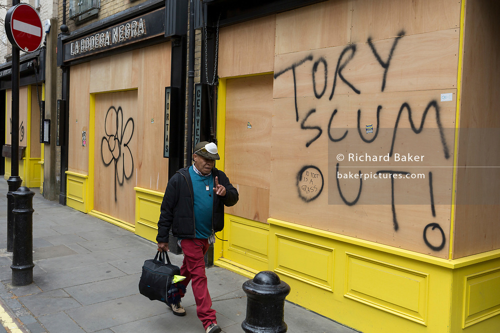 """During the UK's Coronavirus pandemic lockdown and on the day when a further 255 deaths occurred, bringing the official covid deaths to 37,048, <br /> and seen the day after the very unusual press conference by UK Prime Minister's special advisor Dominic Cummings about his breaking of lockdown rules, a workman walks past the message """"Tory Scum Out!"""" which has been written on plyboard on a closed business in Soho, on 26th May 2020, in London, England."""