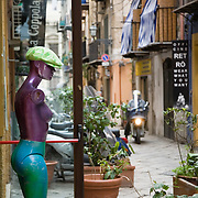 Mannequin watches early morning activity on neighborhood street Via dello Orologio, Palermo, Sicily, Italy