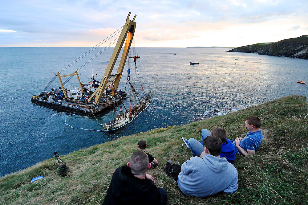 Onlookers view the Astrid wreck being raised by a special crane .<br /> Picture. John Allen