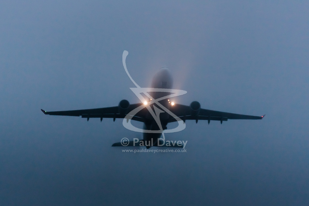 "January 3rd 2015, Heathrow Airport, London. Low cloud and rain provide ideal conditions to observe wake vortexes and ""fluffing"" as moisture condenses over the wings of landing aircraft. With the runway visible only at the last minute, several planes had to perform a ""go-round"", abandoning their first attempts to land. PICTURED: Its landin light cutting their beams into the low cloud, an Airbus A330 takes off from London Heathrow."