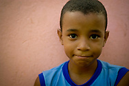 A elementary age Brazilian boy in the Calabar Favela in Salvador, Brazil.  A favela is the Brazilian equivalent of a shanty town.  The majority have electricity, but in most cases it is illegally tapped from the public grid.  The Calabar favela is the oldest favela in Salvador, dating from 1913. Although it was originally built on the outskirts of the city, the city has grown around it, and it is now sandwiched between a rich and a middle class neighborhood.  Calabar is a shining example of community action.  There are no public schools in the favela, so the members of the community have organized their own. It receives no financial assistance from the government, subsisting on the proceeds from bake sales, donations, and grants from non-governmental organizations.