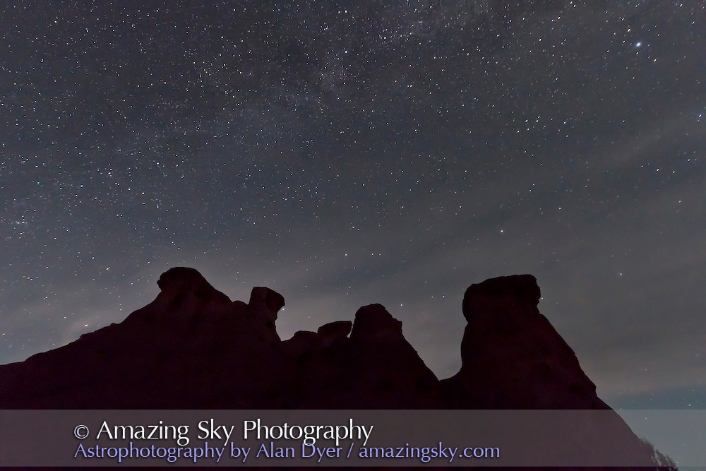 Cassiopeia and the stars of the autumn sky rising behind hoodoo formation at Writing-on-Stone Provincial Park, Alberta, July 22, 2011. This is one frame of a 300 frame time-lapse sequence, taken with the Canon 7D and 10-22mm lens at 10mm, and f/5. Each frame 40 seconds at ISO 2500. Light from rising Moon behind rocks is lighting the sky, with some haze and thin cloud moving through.