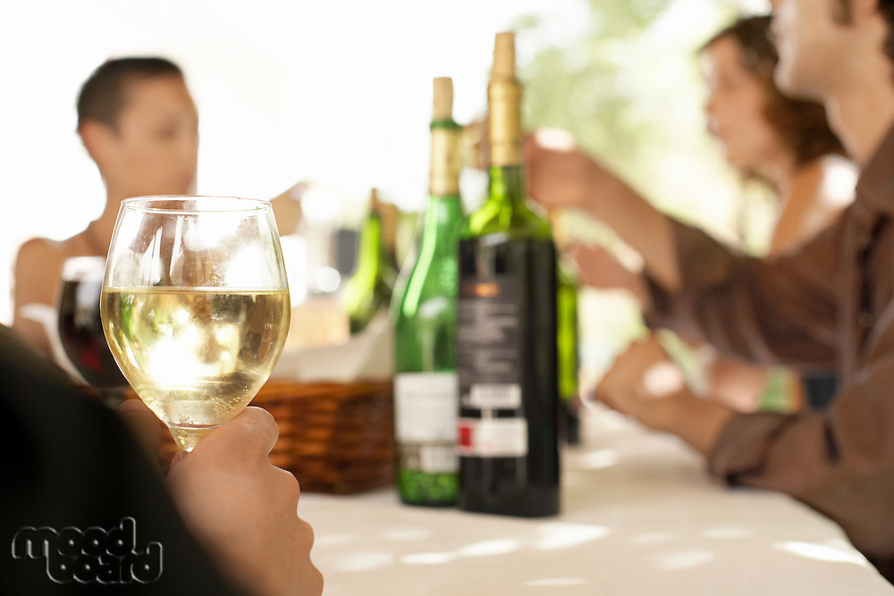 Glass of white wine on table surrounded by group of people.