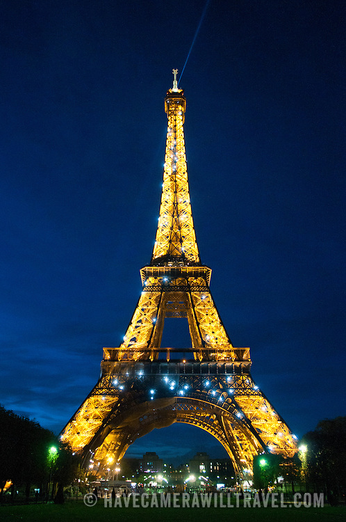 The Eiffel Tower illuminated at night against a deep blue sky of dusk.