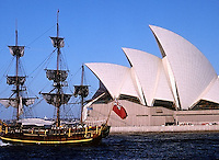 A replica on an ancient tall ship sails past the Opera House in Sydney Harbour.