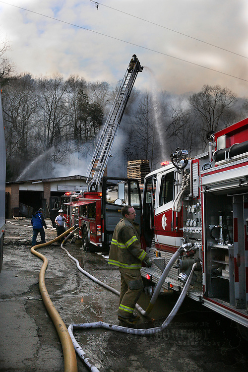Gary Cosby Jr./Decatur Daily   Firefighters from several Morgan and Cullman County volunteer fire departments work to control a fire at Good Hope Pallet Company in Lacon on Highway 31 Saturday.  A firefighter from Vinemont Providence VFD directs a stream on the fire from atop a ladder truck.