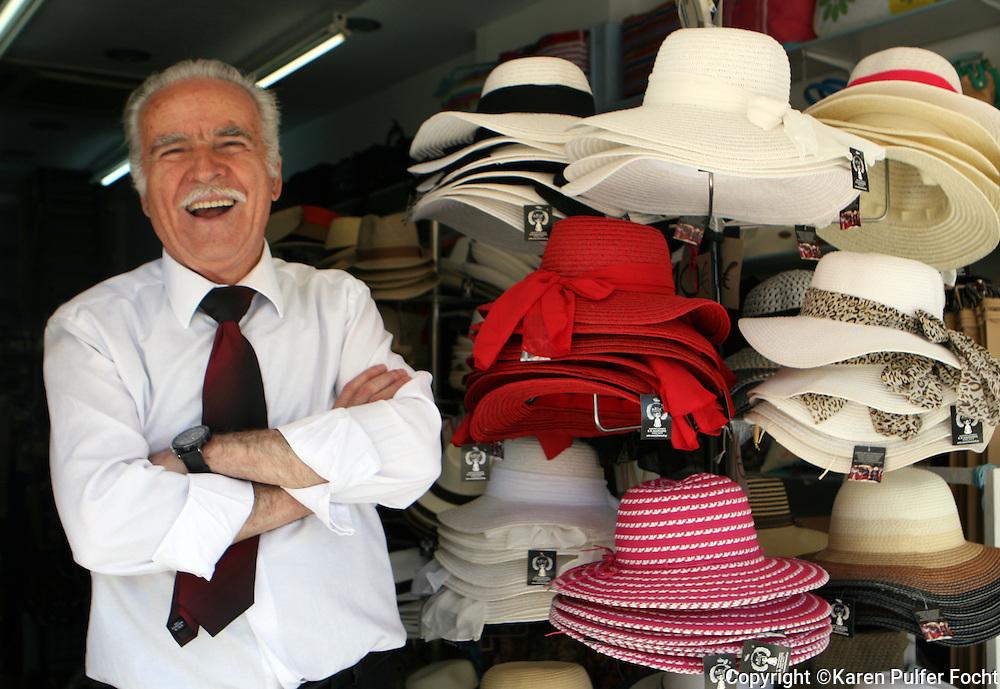 June 1, 2014 - A joyful business man sells some hats on the island of Crete, Greece.