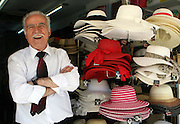 June 1, 2014 - A joyful business man sells some hats on the island of Crete, Greece.