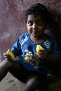 A small boy eats fruit in Russell Market, Bangalore, India