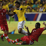 Juan Cuadrado, Colombia, is tackled by Doneil Henry, Canada, during the Columbia Vs Canada friendly international football match at Red Bull Arena, Harrison, New Jersey. USA. 14th October 2014. Photo Tim Clayton