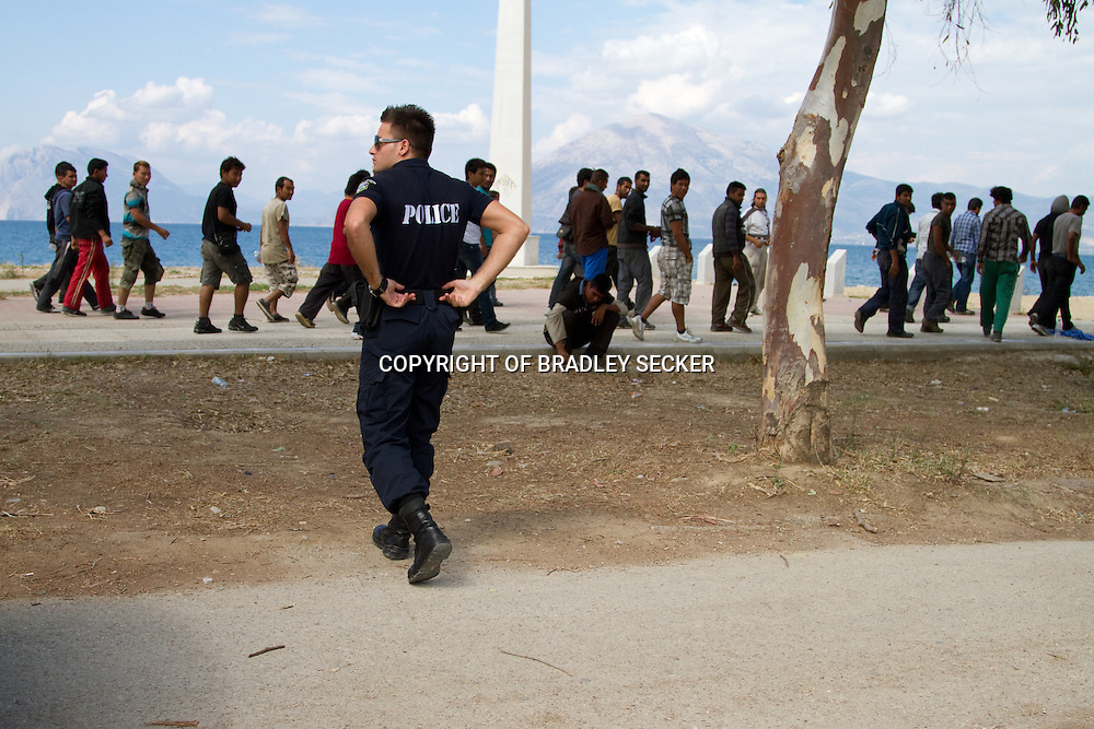 Patras, Greece - Police order a large group of Afghan migrants and refugees away from a main road nicknamed 'the runway', from where they hope to climb onto lorries and trucks stuck in traffic and headed for the international port.
