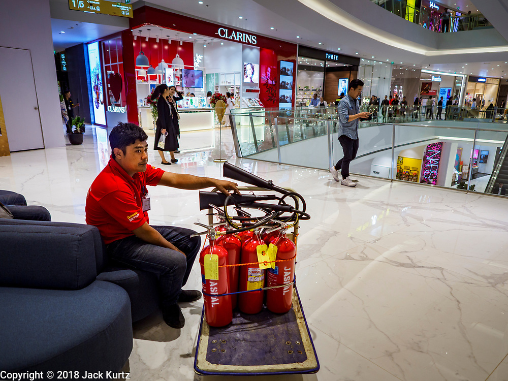 09 NOVEMBER 2018 - BANGKOK, THAILAND: A worker sets out fire extinguishers in the new ICONSIAM mall in Bangkok. ICONSIAM opened November 9. ICONSIAM is a mixed-use development on the Thonburi side of the Chao Phraya River. It includes two large malls, with more than 520,000 square meters of retail space, an amusement park, two residential towers and a riverside park. It is the first large scale high end development on the Thonburi side of the river and will feature the first Apple Store in Thailand and the first Takashimaya department store in Thailand.     PHOTO BY JACK KURTZ