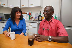 Elderly black man with white woman carer at home in kitchen