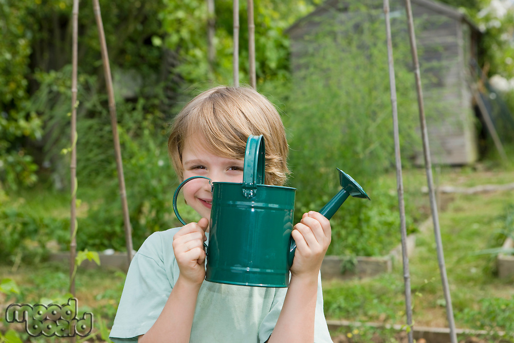 Boy holding watering can in garden