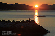Man stands on breakwater at Telegrafbukta at the south end of Tromsoya island on January 21st watching return of the sun after its two-month absence; Tromso, Norway.