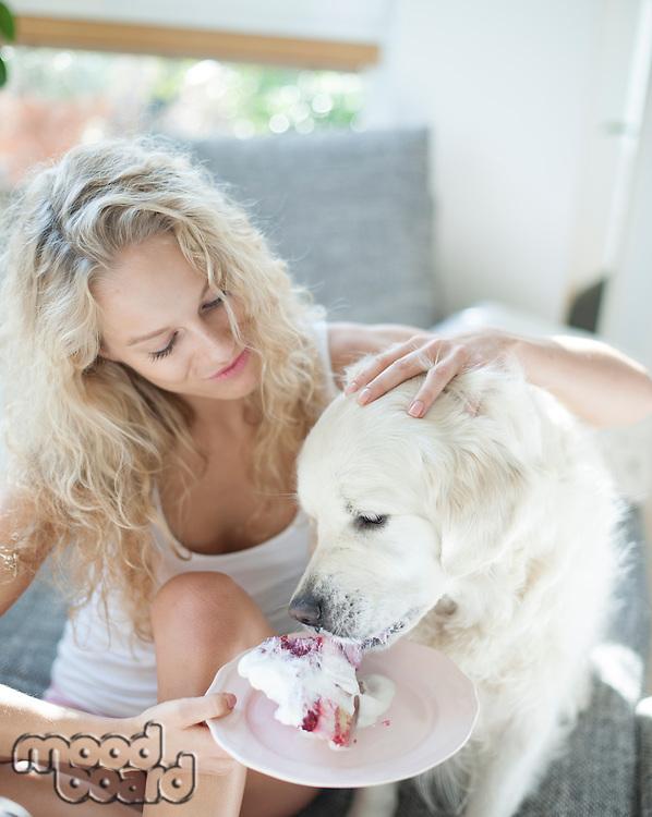 Beautiful woman feeding cake to dog in house