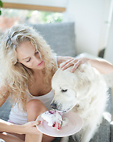 Beautiful woman feeding cake to dog in house