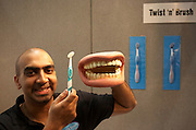 A new toothbrush twist concept is demonstrated by an entrepreneur at an inventors fair in Alexandra Palace, London