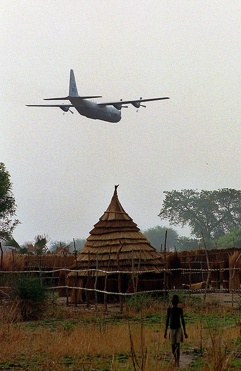 csz980429sudan1c:a c130 hercules flies over a village on its way to drop 16 tonnes of grain at a world vision food distributuion site, pre famine conditions in bahr el ghazal regeon of southern sudan threaten the lives of 500,000 people: pic craig sillitoe: story helen signy (smh): news extra melbourne photographers, commercial photographers, industrial photographers, corporate photographer, architectural photographers, This photograph can be used for non commercial uses with attribution. Credit: Craig Sillitoe Photography / http://www.csillitoe.com<br />