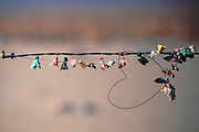 Small prayer flags and a wire heart on a barbed wire fence at the Manzanar Cemetery, Manzanar National Historic Park, Owens Valley, California