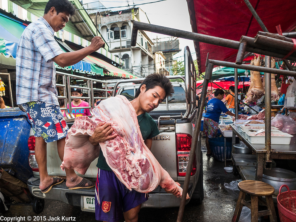 """12 JUNE 2015 - BANGKOK, THAILAND: Delivery of fresh pork in Khlong Toey Market in Bangkok. Khlong Toey (also called Khlong Toei) Market is one of the largest """"wet markets"""" in Thailand. The market is located in the midst of one of Bangkok's largest slum areas and close to the city's original deep water port. Thousands of people live in the neighboring slum area. Thousands more shop in the sprawling market for fresh fruits and vegetables as well meat, fish and poultry.          PHOTO BY JACK KURTZ"""