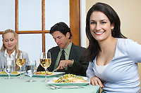 Group of people in restaurant, one woman looking at camera