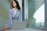 Business woman using laptop sitting on window ledge
