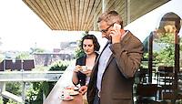 Österreich, telefonierender Geschäftsmann und Geschäftsfrau vor Restaurant, nach dem Meeting, informelle, entspannte Atmosphäre, Kaffeepausegg